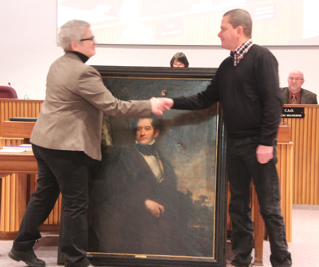 Donor with gifts of art shaking hands with Curator, Lisa Daniels