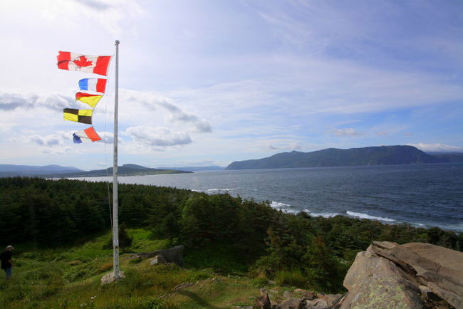 Flags on hillside overlooking water
