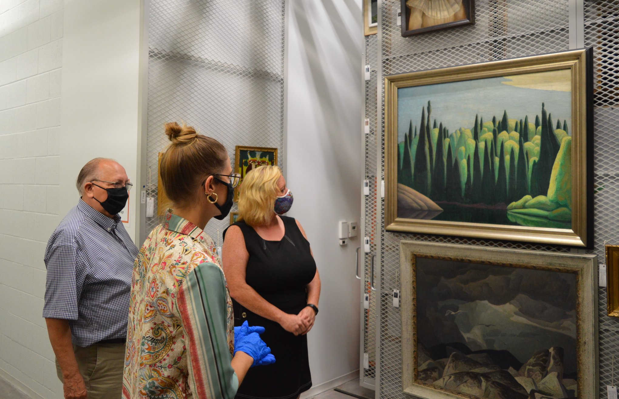 Curator Sonya Blazek showing Minister Lisa MacLeod and Bob Bailey works from the permanent collection